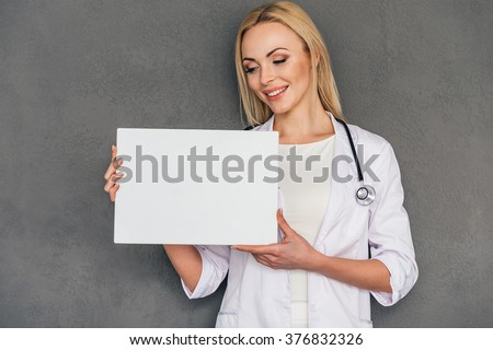 Best prescription for you! Beautiful young female doctor holdingcopy space and looking at it with smile while standing against grey background