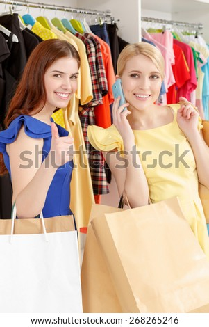 Best shopping. Two smiling women happily holding paper bags copyspace while one shows thumb up and the other speaks over the phone - stock photo