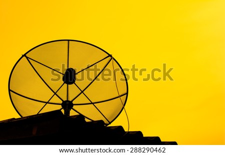 Best signal with silhouette of satellite dish on the roof at home with golden sky on sunset time - stock photo