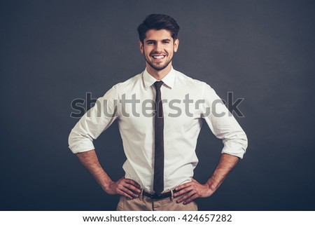 Best smile. Confident young handsome man keeping arms akimbo and looking at camera with smile while standing against grey background - stock photo