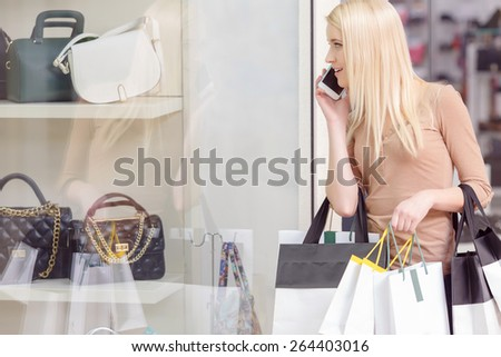 Best time for shopping. Beautiful blond woman holding shopping bags copy space and talking over the phone - stock photo