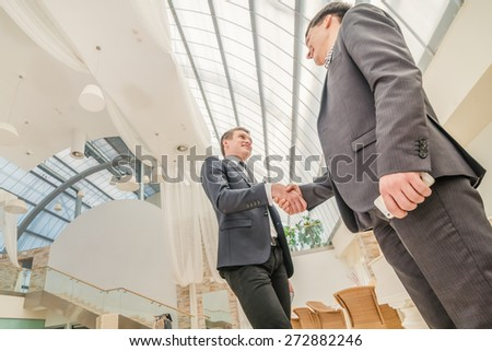 Best top deal! Two young businessman standing opposite each other and shake their hands. Smiling young people into the camera. Close-up view from below - stock photo