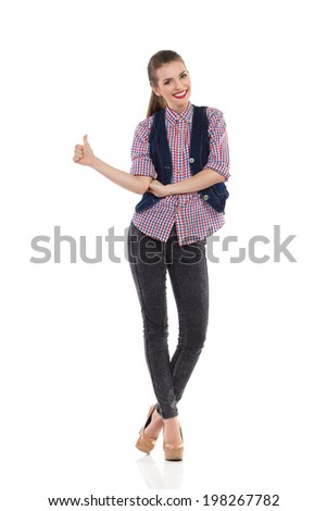 Best wishes! Smiling young woman showing thumb up. Full length studio shot isolated on white. - stock photo