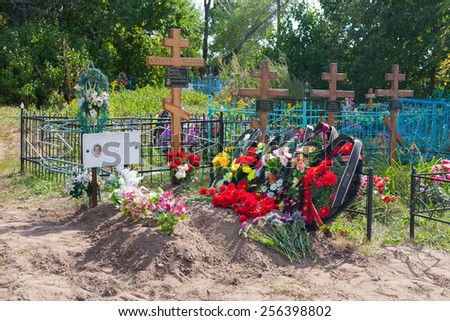 BESTUZHEVO, RUSSIA - AUGUST 26: Graves, flowers, wreaths and crosses in the cemetery on August 26, 2014 in Bestuzhevo village. - stock photo