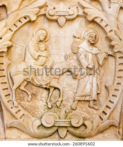 """BETHLEHEM, ISRAEL - MARCH 6, 2015: The flight of Holy family to Egypt. The relief on the portal in chapel of  """"Milk Grotto"""" cave. The church was designed by architects Louis Lions and Chiara Rovati, - stock photo"""