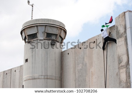 BETHLEHEM, PALESTINIAN TERRITORIES - MARCH 30: A Palestinian scales the Israeli separation wall and plants his flag atop the Bethlehem checkpoint during Land Day protests on March 30, 2012. - stock photo