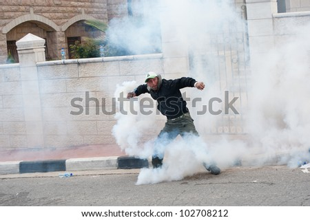 BETHLEHEM, PALESTINIAN TERRITORIES - MARCH 30: A Palestinian throws aside a tear gas grenade fired by Israeli soldiers at the Bethlehem checkpoint during Land Day protests on March 30, 2012. - stock photo