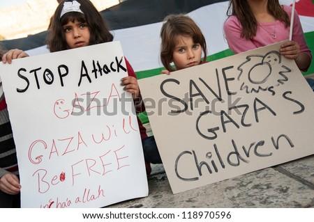 BETHLEHEM, PALESTINIAN TERRITORIES - NOV. 15: Unidentified Palestinian children hold signs protesting Israeli military strikes on Gaza, during a vigil in Bethlehem's Manger Square, November 15, 2012. - stock photo