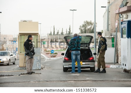 BETHLEHEM, PALESTINIAN TERRITORY - JANUARY 28: A Palestinian man opens his car for inspection at the Israeli military checkpoint controlling movement between Bethlehem and Jerusalem, January 28, 2013. - stock photo