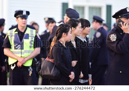 BETHPAGE, LONG ISLAND - MAY 7 2015: a formal viewing for slain NYPD officer Brian Moore, attended by thousands of police officers from North America.Pei Xia Chen (center), widow of Wenjian Liu arrives - stock photo