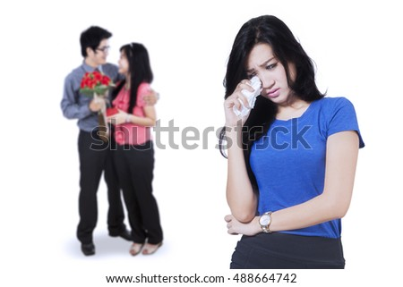 Betrayal concept. Sad woman crying in front of young couple standing on the back, isolated on white background