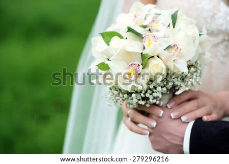 Betrothed pair holding a delicate bouquet of roses and orchid outdoor in pastel colours on green holiday background copyspace, horizontal picture - stock photo