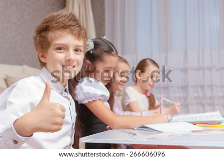 Better than at school.  Small smiling schoolboy showing thumbs up with his friends on the background doing tasks  - stock photo