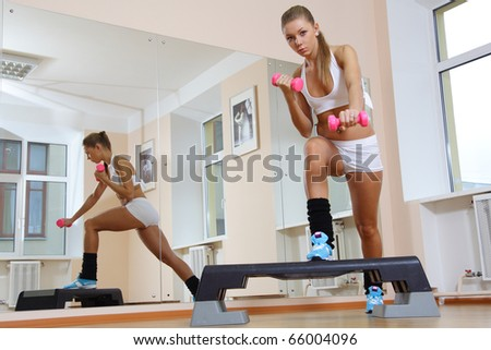 Beutiful blonde girl on step hold dumbbells  in fitness gym - stock photo