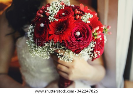 Beutiful bride in white dress holding wedding bouquet red roses closeup - stock photo