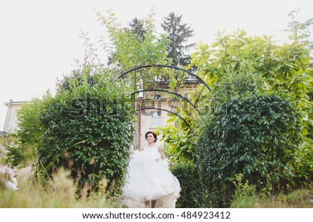 Beutiful bride raises her dress walking out of green bushes