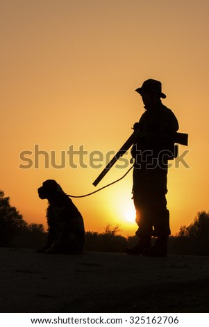 Beutiful sunset of hunter with a dog and gun