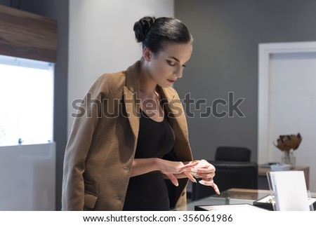 beutiful winter dressed woman , inside a jewellery , trying some rings to buy ,