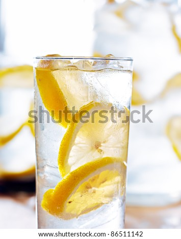 beverage- cold glass of lemonade closeup with pitcher in background - stock photo