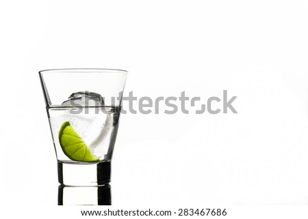 Beverage with lime and ice in glass, isolated on white background - stock photo
