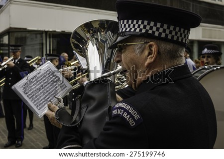 BEVERLEY, UK - MAY 02, 2015: An officer of the Humberside Police Band plays trombone in a public performance during the first Tour de Yorkshire cycle race on May 02, 2015 in Beverley, Yorkshire, UK.