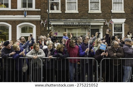 BEVERLEY, UK - MAY 02, 2015: Spectators enjoy the Tour de Yorkshire cycle race during the wait for the main peloton of cyclists along the North Bar Within on May 02, 2015 in Beverley, Yorkshire, UK. - stock photo