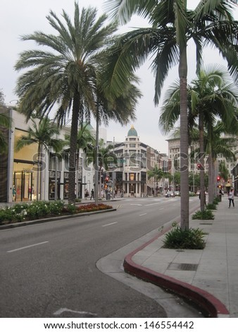 BEVERLY HILLS, CA - JULY 10: Rodeo Drive in Beverly Hills as seen on July 10, 2013. Rodeo Drive is an affluent shopping district known for designer label and haute couture fashion. - stock photo