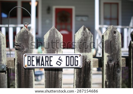 Beware of Dog sign for security on wooden fence outside of home - stock photo