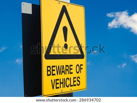 beware of vehicles road sign closeup - stock photo