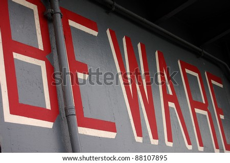 BEWARE (painted on the metal siding of the tower of the USS Intrepid)