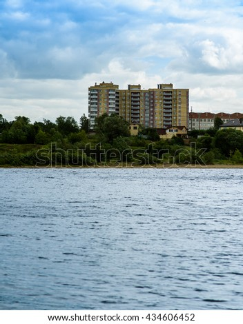 beyond the river is high-rise building on blue sky background and clouds - stock photo