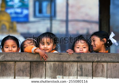 BHAKTAPUR, NEPAL - JANUARY 8: Nepalese schoolgirls poses for a photo during their breaktime on January 8, 2010 in Bhaktapur, Kathmandu Valley, Nepal.  - stock photo