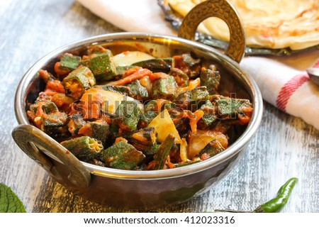 Bhindi Masala / Okra Fry - Deep fried Okra sauteed with tomatoes and spices served with Paratha on side, selective focus