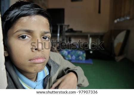 BHOPAL- DECEMBER 7:  11 years old Azhar suffering from cerebral palsy waiting eagerly inside a clinic for his ride to his home in  Bhopal - India on December 7, 2010. - stock photo