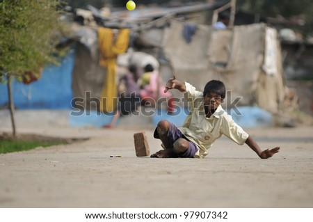 BHOPAL- NOVEMBER  28:  Sachin a 16 years old Bhopal gas victim who allegedly lost strength in his limbs  because of water contamination playing cricket in Bhopal - India on November 28, 2010. - stock photo