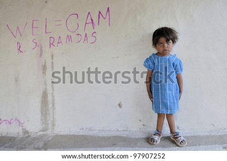 BHOPAL- NOVEMBER 14:  7years old Meenakshi suffering  from Osteoporosis-a disease in her bones standing  infront of her house  in Bhopal - India on November 14, 2010. - stock photo