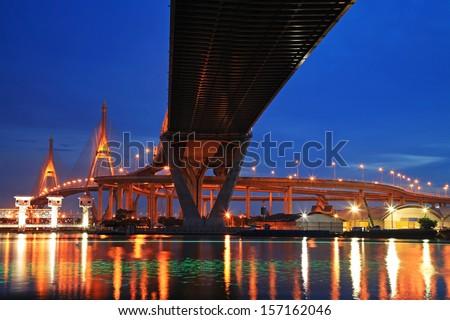 Bhumibol Suspension Bridge, aka Industrial Ring Road, across Chao Phraya river with light trail at twilight in Bangkok, Thailand - stock photo
