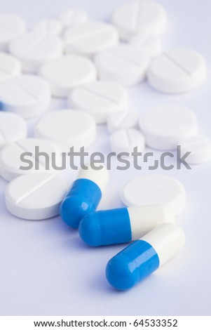 bi-color blue white three capsules and tablets on a white background