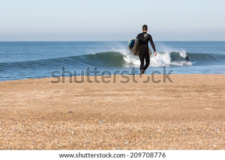BIARRITZ, FRANCE, DECEMBER 3: Unidentified young man with surf board on December 3, 2013. Biarritz beach, France.Biarritz is one of the most popular surfing areas of France. - stock photo