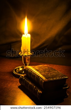 Bible and old books and candle on a wooden table. Focus on the old books, image vignetting and in yellow toning