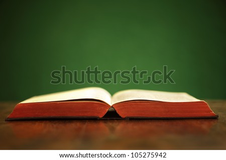 Bible on table with green background and copy space - stock photo