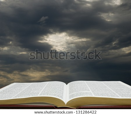 Bible open with dark sky in the background - stock photo