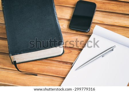 Bible study materials - a Bible, notebook and a smartphone over a wooden surface. - stock photo