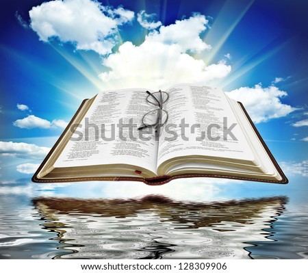 Bible with blue sky and white clouds with reflection in water - stock photo