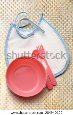 Bibs, bowl and spoon for baby in closeup - stock photo