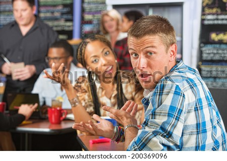Bickering young married couple sitting in coffee house - stock photo