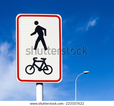 Bicycle and pedestrian lane road sign on pole post, bike cycling and walking walkway footpath route traffic roadside signal. - stock photo