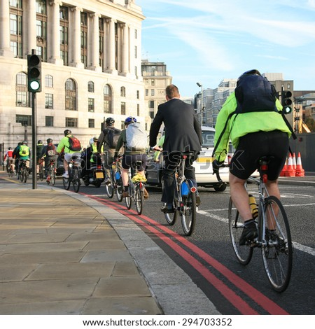 Bicycle commuters on their way to work after crossing Blackfriars bridge in early morning.