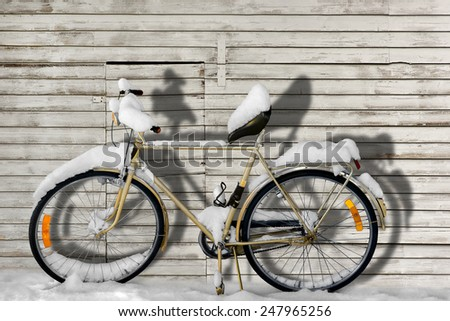Bicycle covered in snow wooden white wall in sunshine