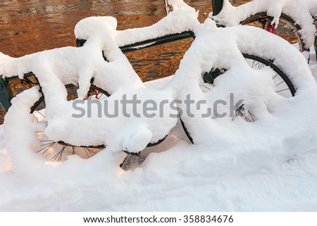 Bicycle covered with snow in front of an Amsterdam canal - stock photo